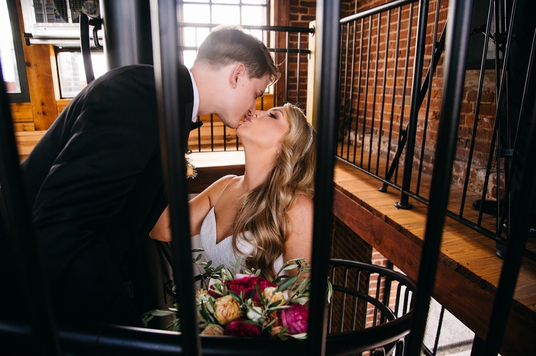 Bride and groom kiss at the top of the spiral staircase of their wedding at the Turnbull building.