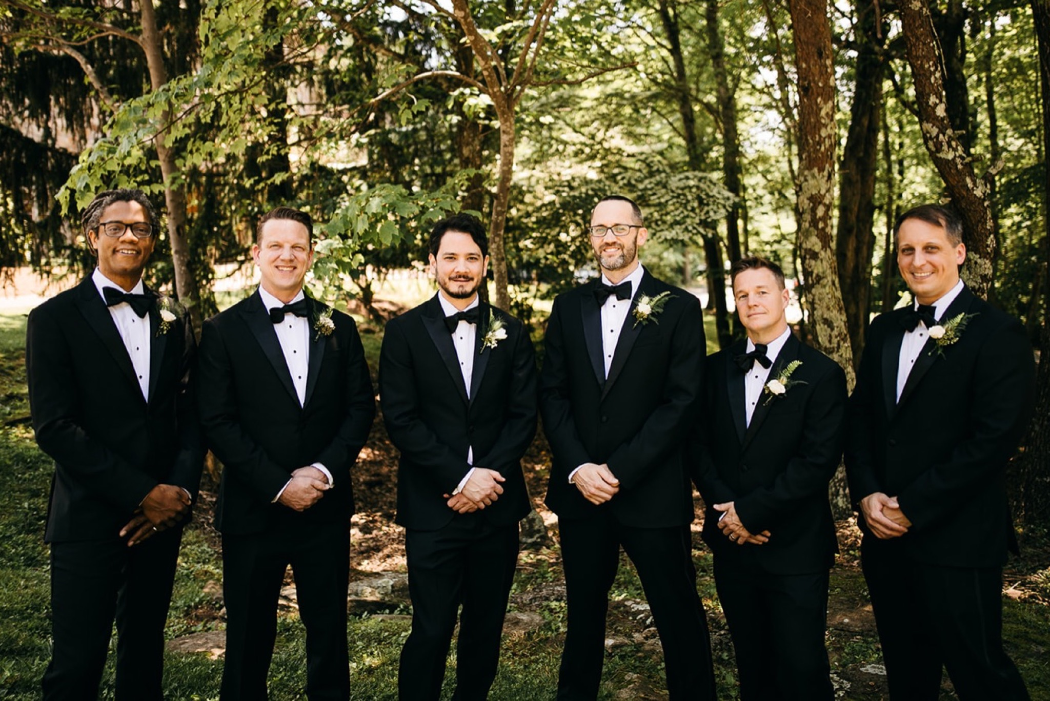 groom and groomsmen wear classic black tuxedos and pose for bridal party shots