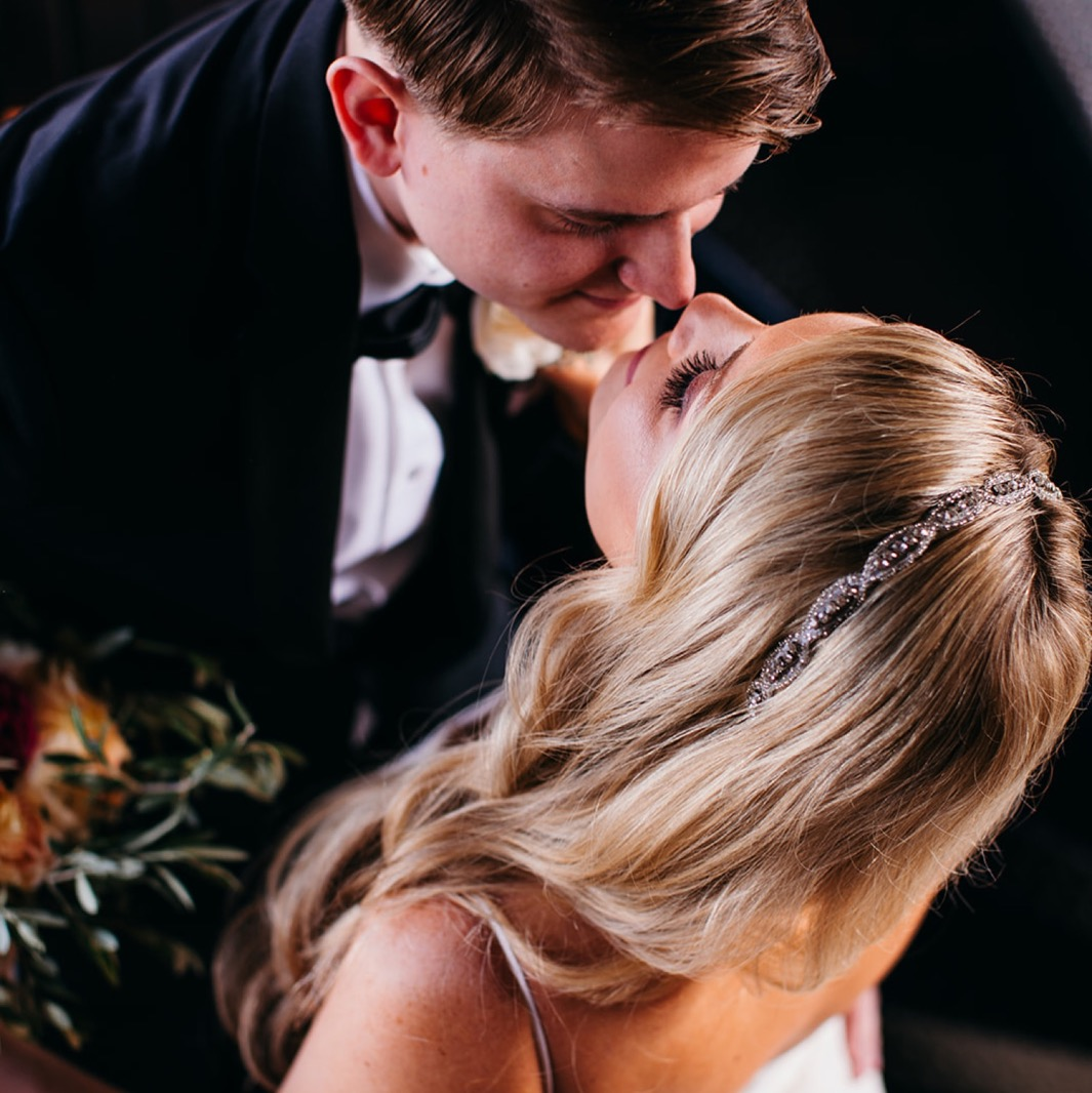 Bride and groom touch noses at the top of the spiral staircase of their wedding at the Turnbull building.