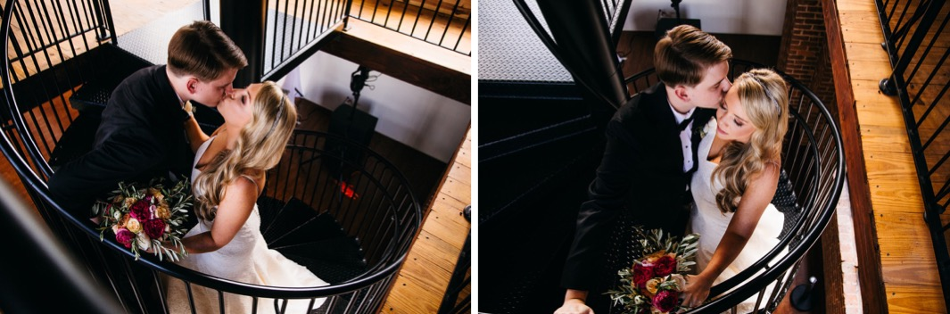 Bride and groom kiss at the top of the spiral staircase of their wedding at the Turnbull building. Groom kisses brides cheek. Bride and groom stand at the top of the spiral staircase and smile.