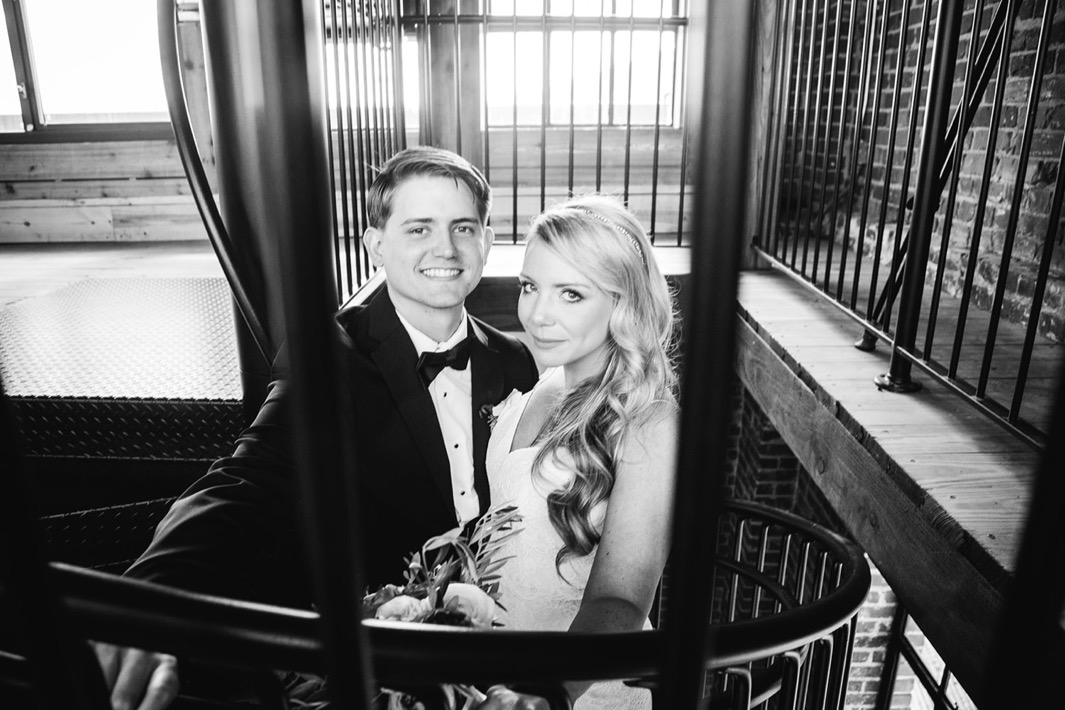 Bride and groom stand at the top of the spiral staircase and smile.