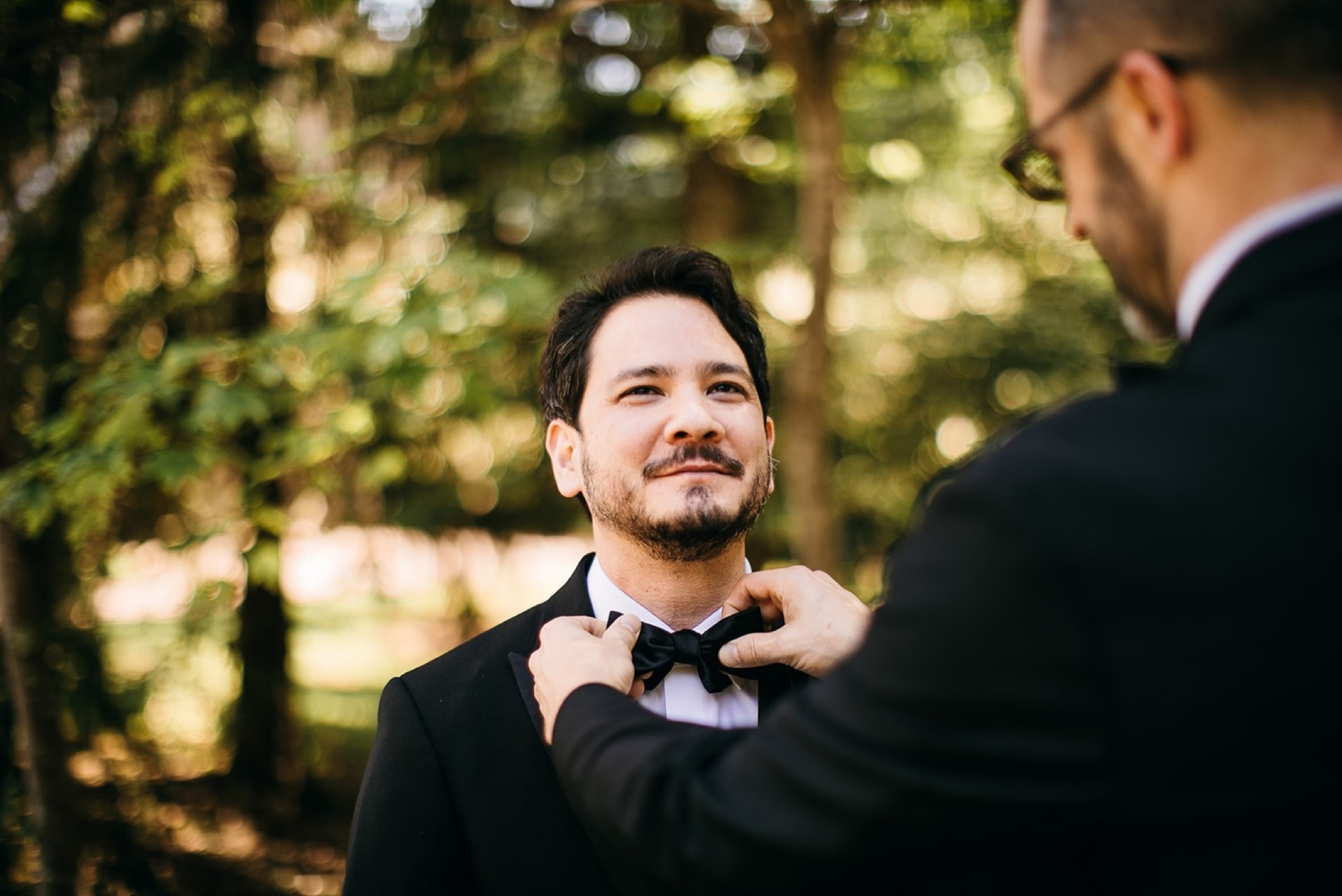 a man helps straighten the black bowtie his friend is wearing