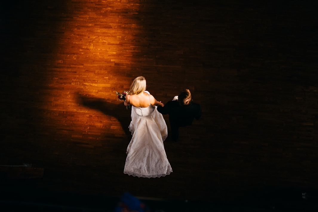 Bride and groom hold hands and walk across the hardwood floor at their wedding in the Turnbull building.