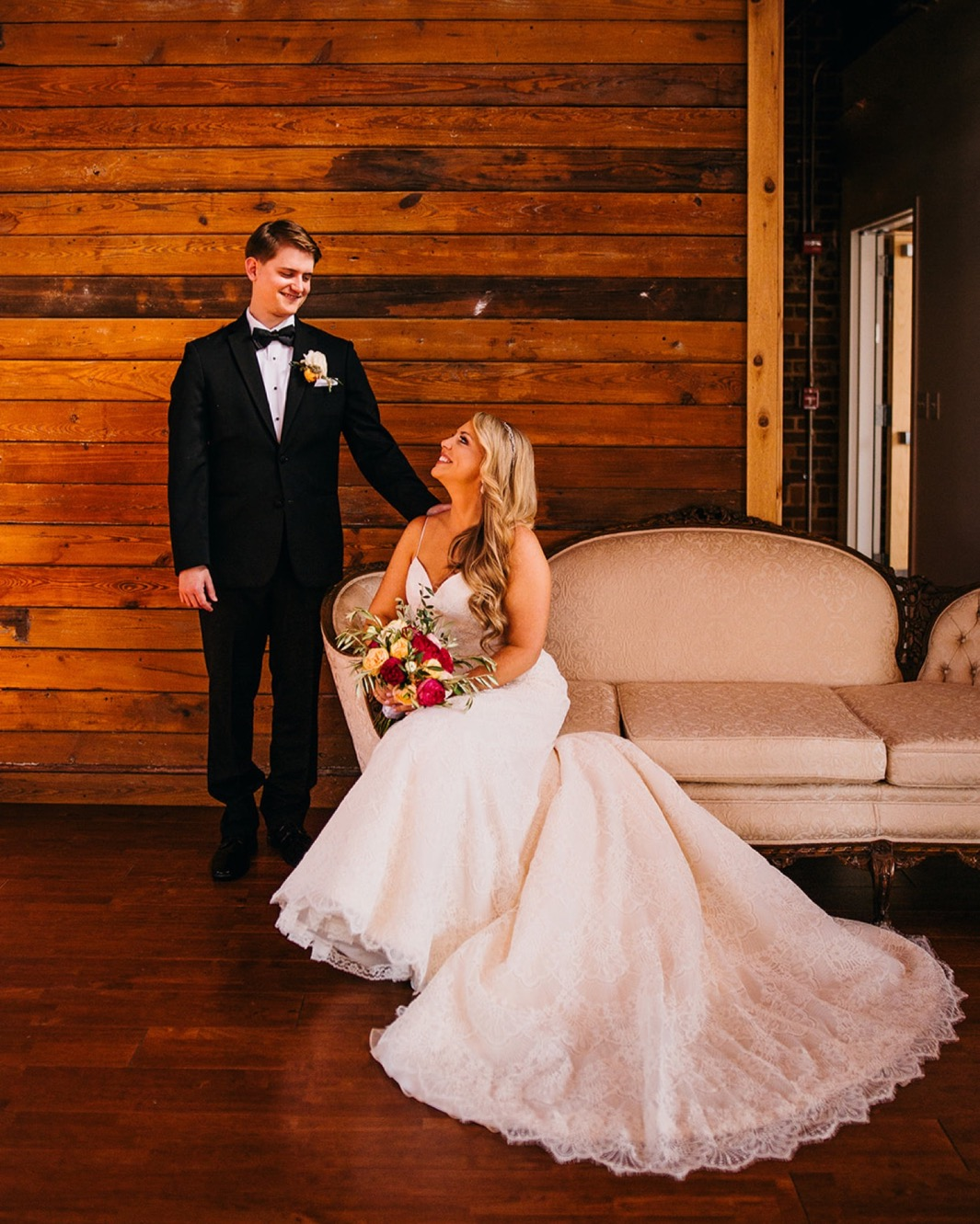 Bride sits on a chaise and smiles at the groom while the groom stands next to her.