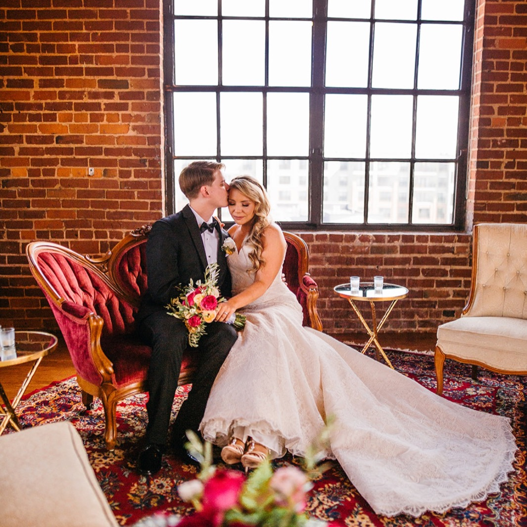 Bride and groom sit on the red velvet chaise as the groom kisses the brides temple during their wedding at the Turnbull building.