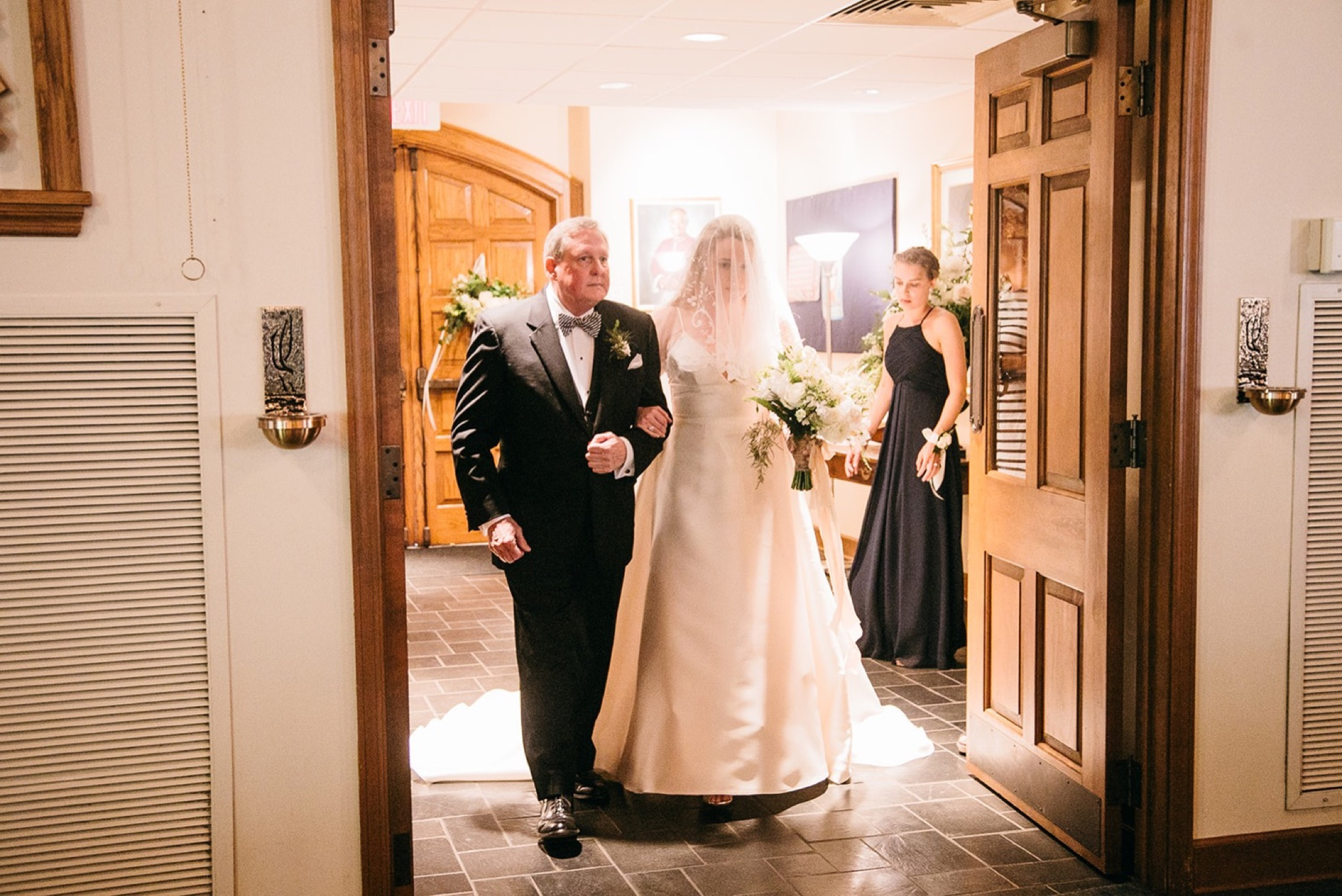 bride holds her father's arm as they walk between two wooden doors into Our Lady of the Mount Catholic Church