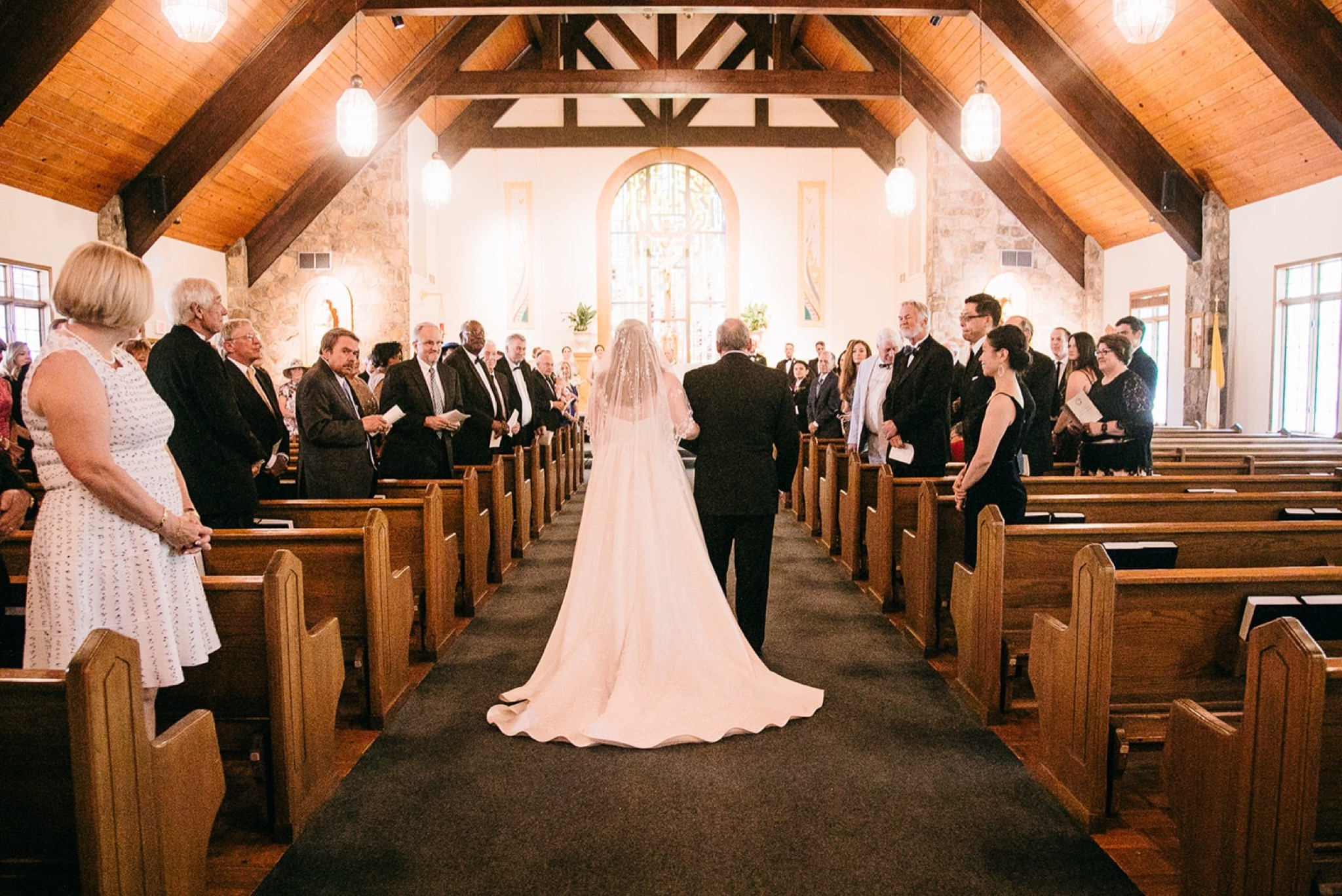 bride and her father walk between wooden pews as wedding guests stand and watch