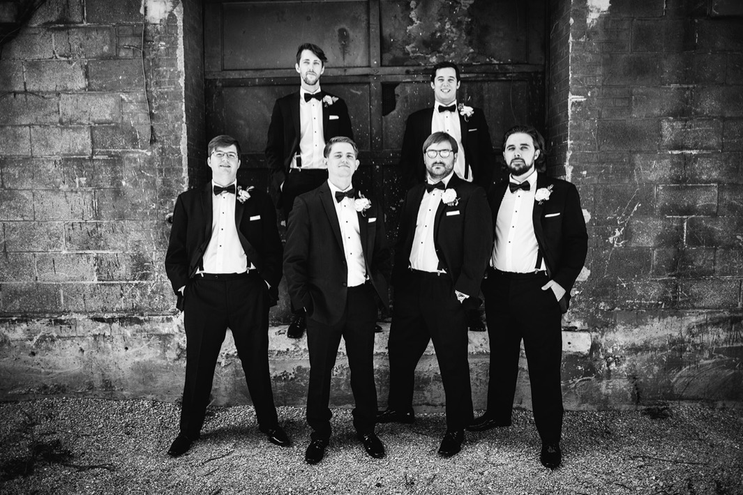 Groom poses for a photo with his groomsmen outside the wedding at the Turnbull building.