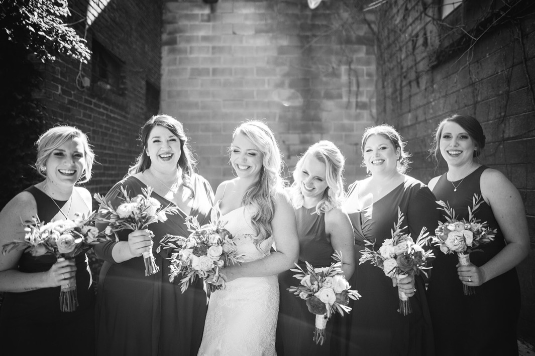 Bride and bridesmaids laugh while holding their bouquets outside the Turnbull building wedding.