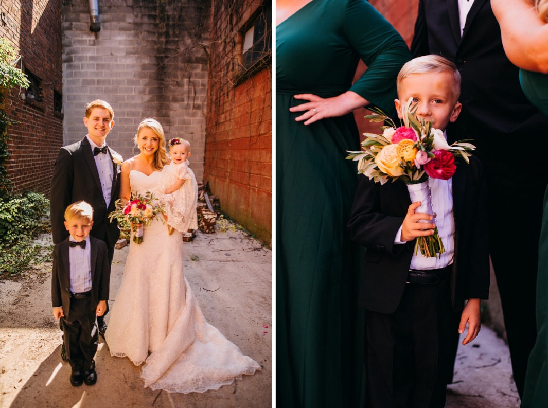Bride and groom smile as they stand with the flower girl and ring bearer outside the wedding at the Turnbull building. Close up of the ring barer holding the brides pink and yellow rose bouquet.