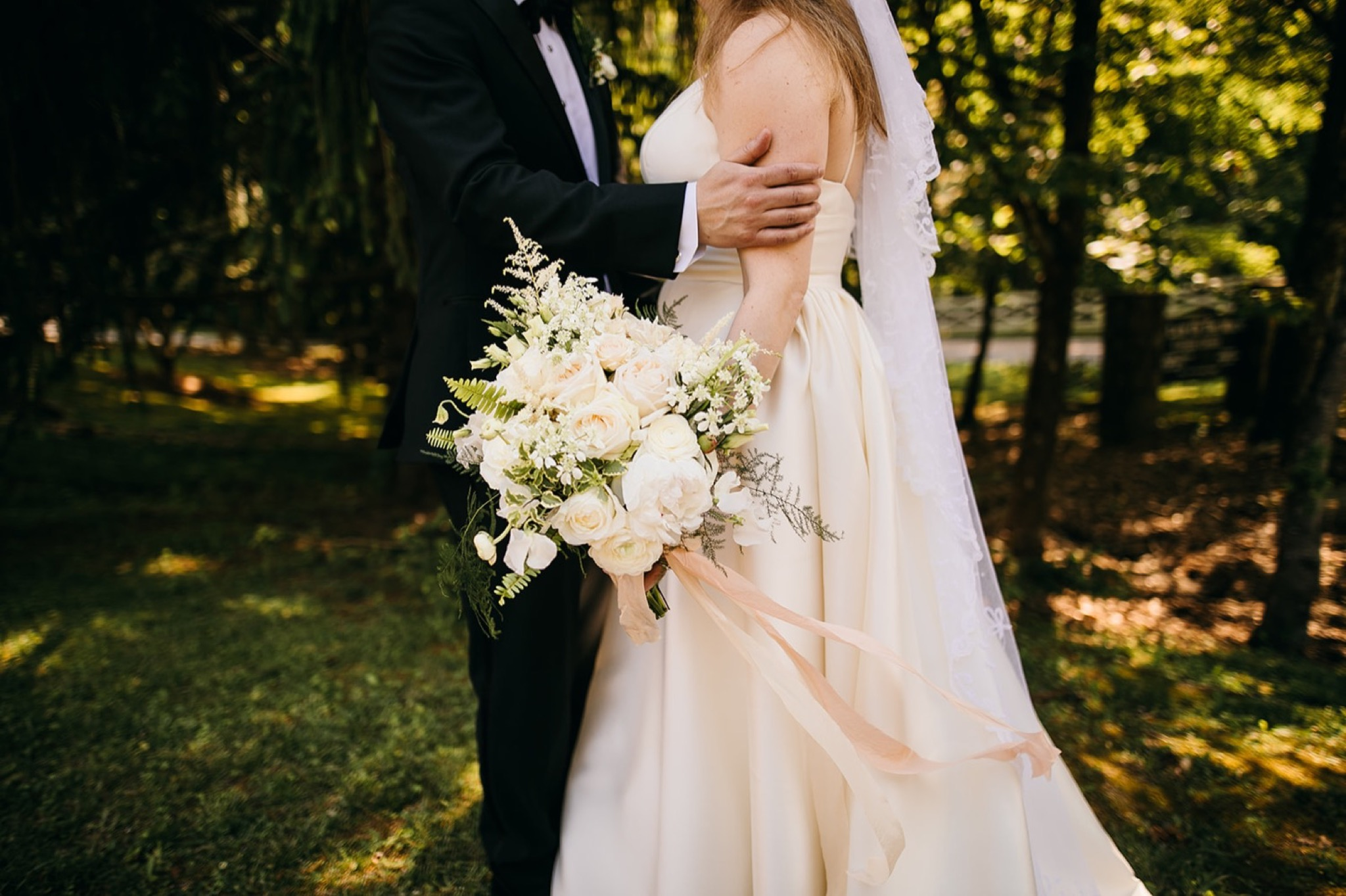 bride holds her bouquet of white flowers and light pink ribbon as groom holds her arm