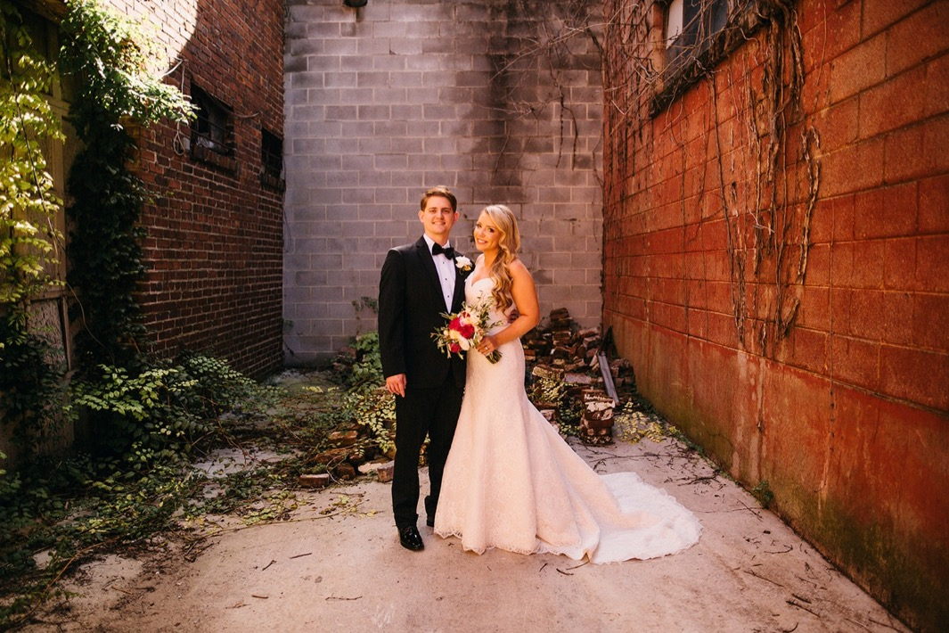 Bride and groom smile as they stand in an alley way outside their wedding at the Turnbull building.