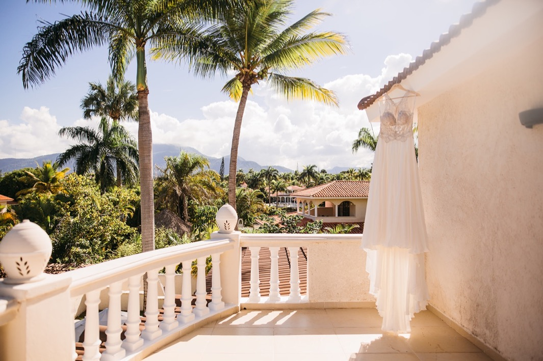 wedding dress hangs from Spanish tile roof on balcony overlooking palm trees and mountains in the Dominican Republic