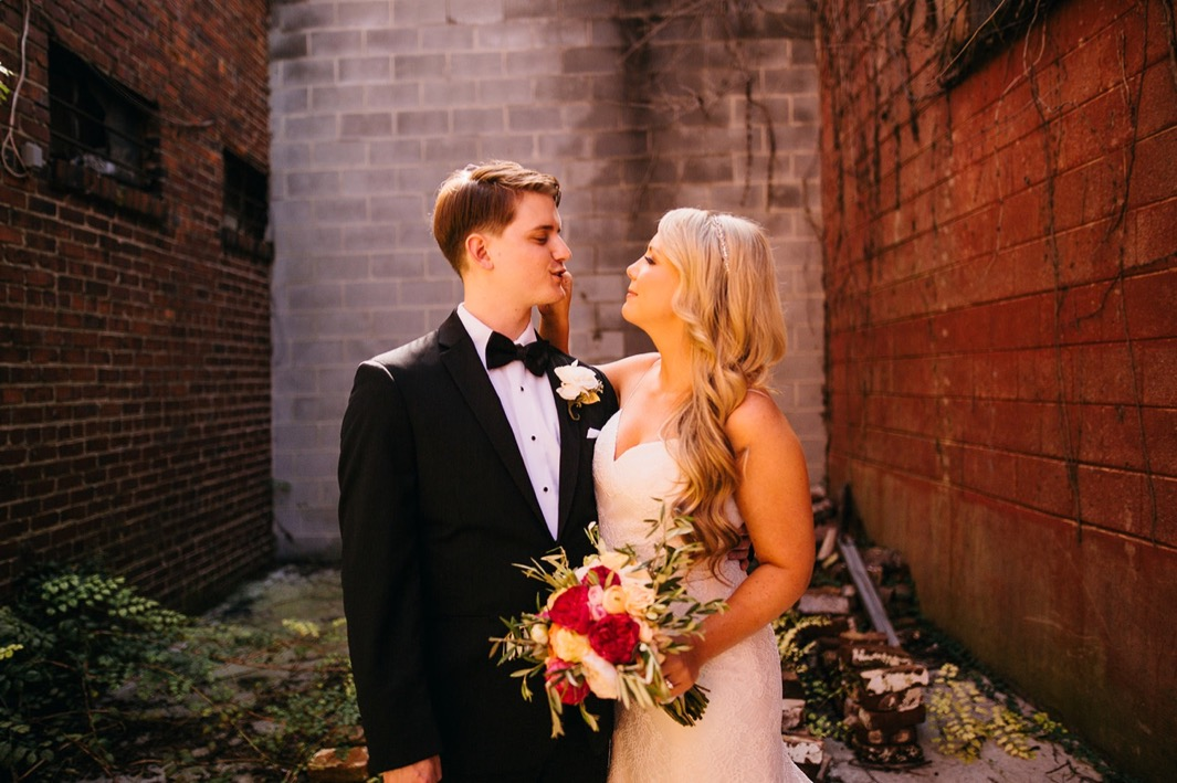 Groom makes a silly face at the bride as she smiles outside their wedding at the Turnbull building.