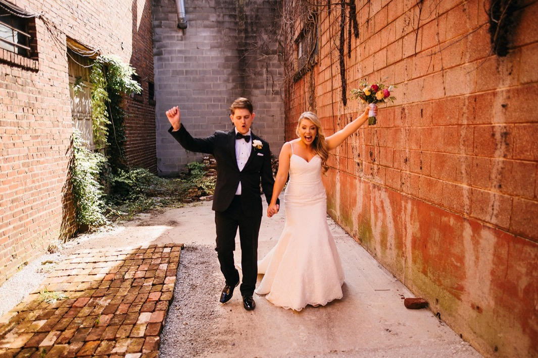 Bride and groom throw their hands up and cheer outside their Turnbull building wedding.
