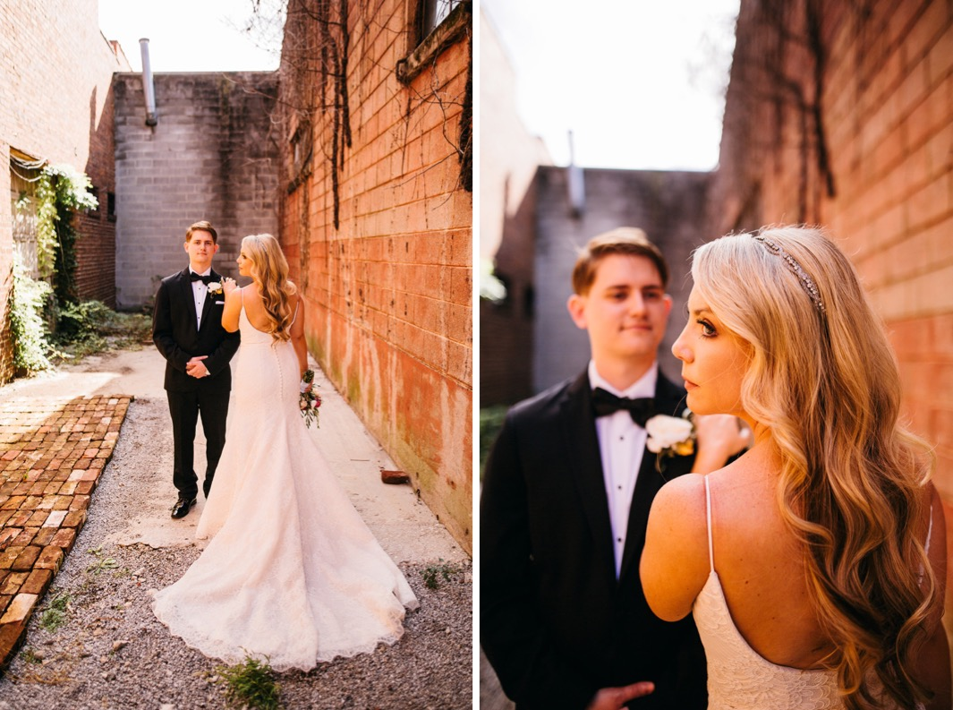 Bride puts her hand on the grooms shoulder and shows off the back of her fitted mermaid style wedding dress.