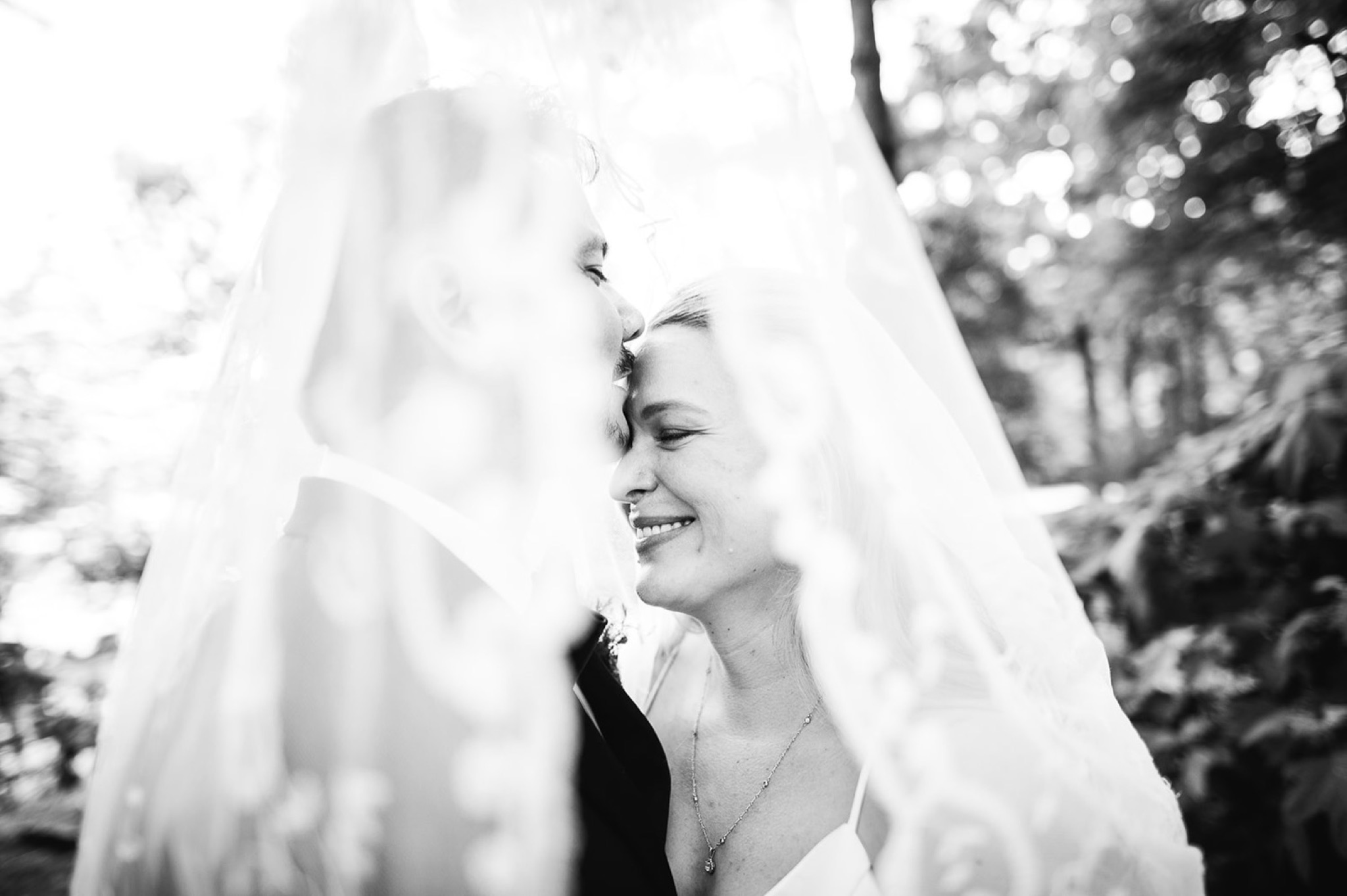 under lacy bridal veil groom kisses bride's forehead as she grins