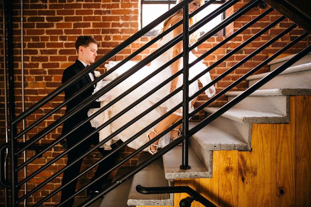 Groom holds the bottom of the brides wedding dress as they walk up the stairs of their wedding at the Turnbull building.