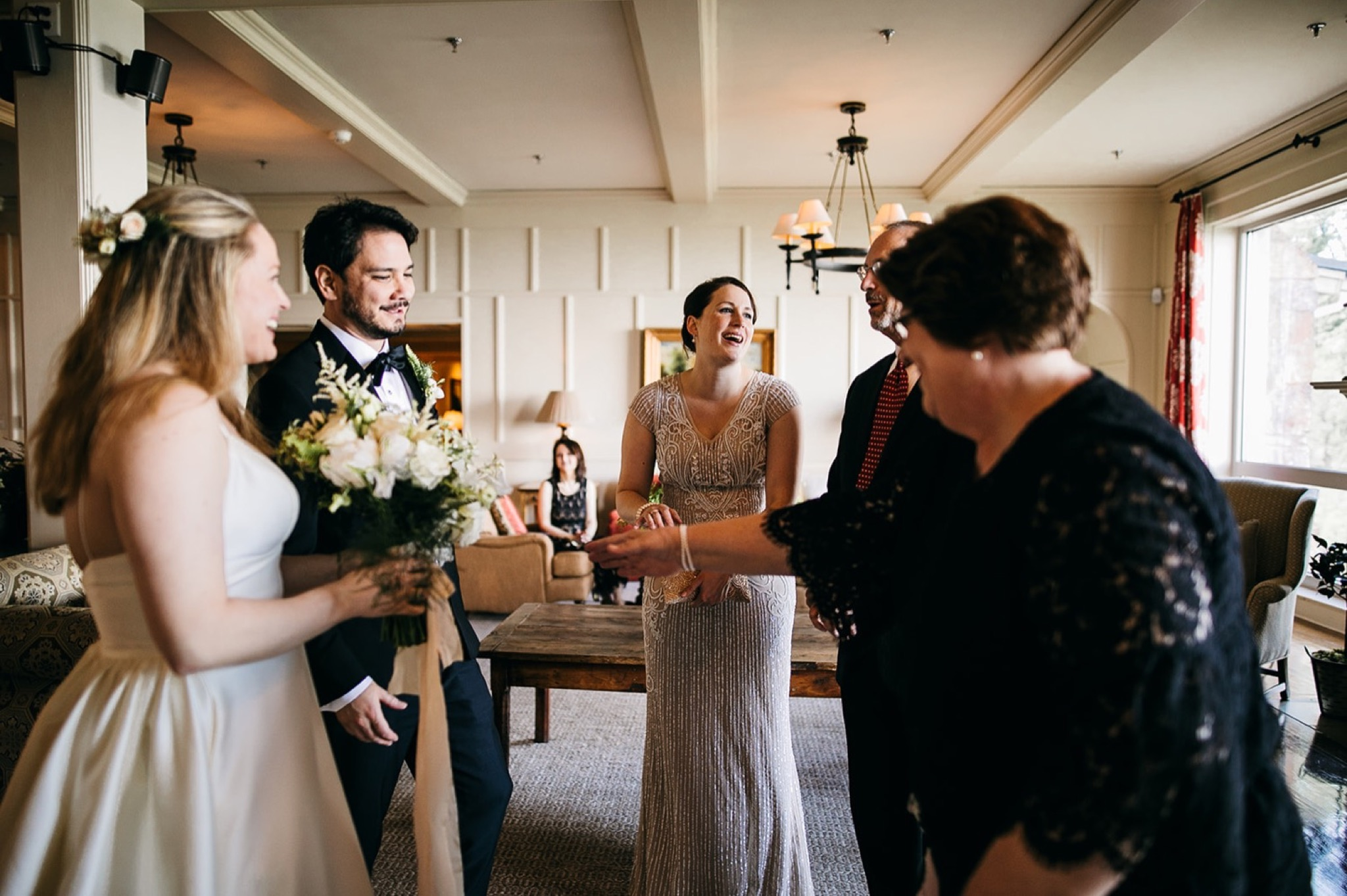 bride and groom smile at friends and family who congratulate them