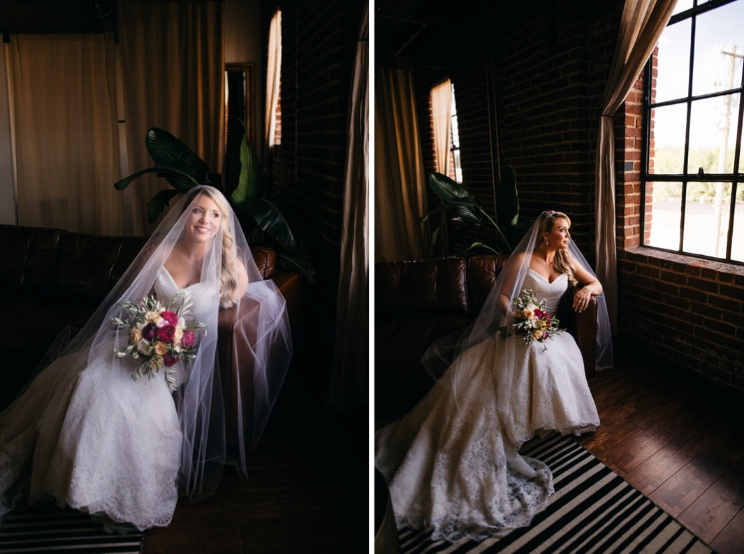 Bride sits on a love seat smiling with her veil over her face as she holds her bouquet.