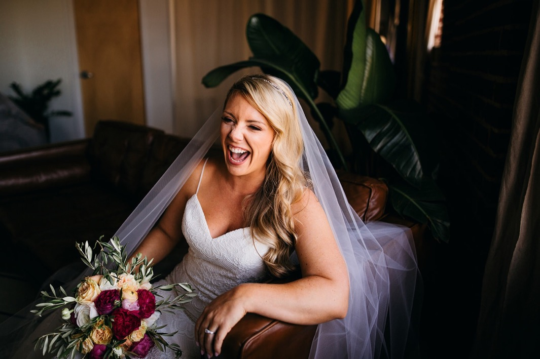 Bride sits on a love seat and laughs while holding her bouquet at her wedding at the Turnbull wedding.