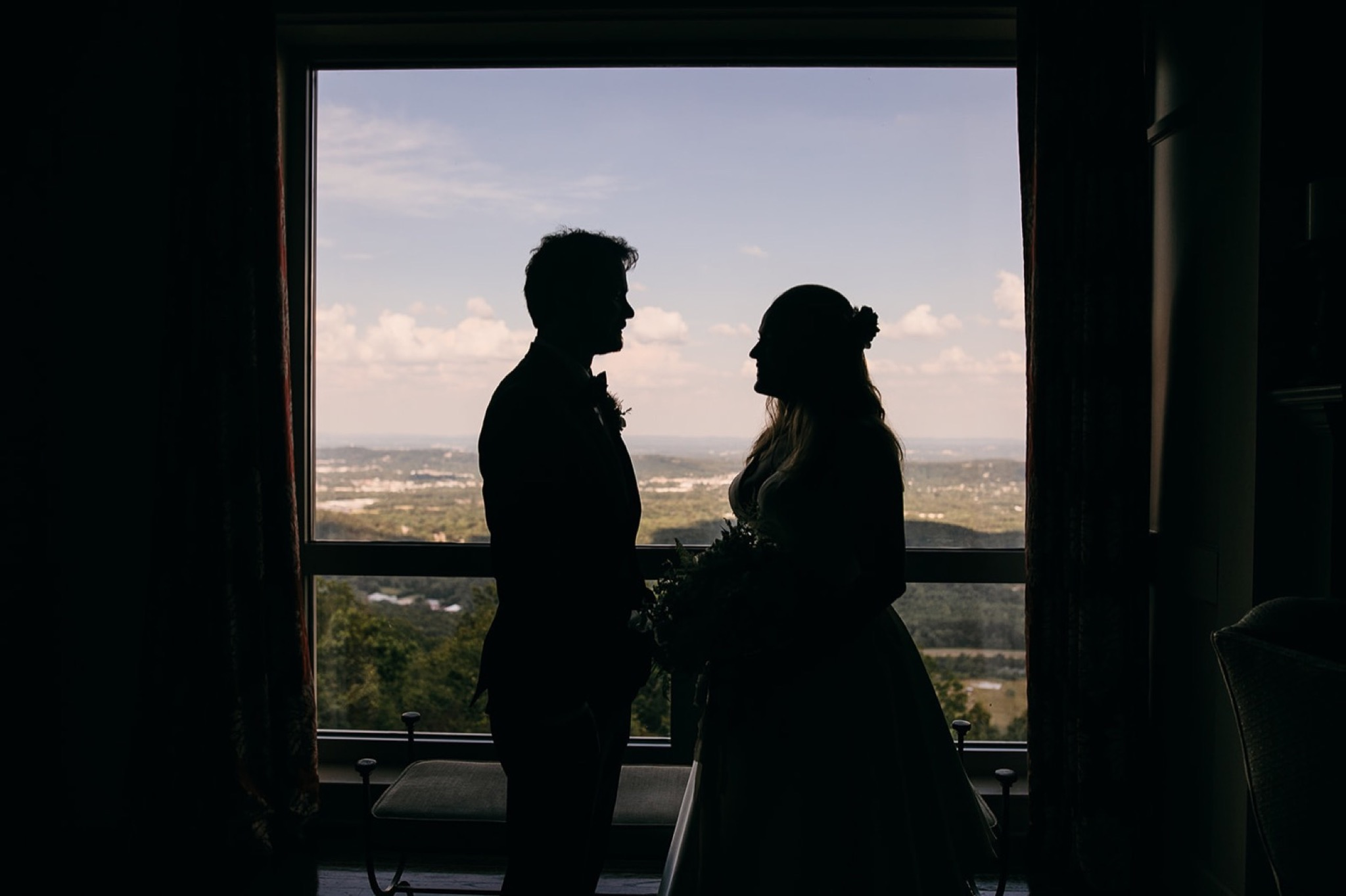 bride and groom stand silhouetted against a floor-to-ceiling window