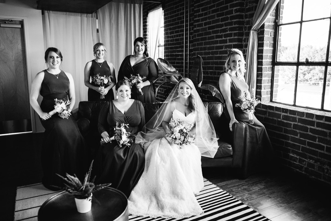 Black and white photo of the bride and her bridesmaids sitting on a love seat and similing before the wedding at the Turnbull building.