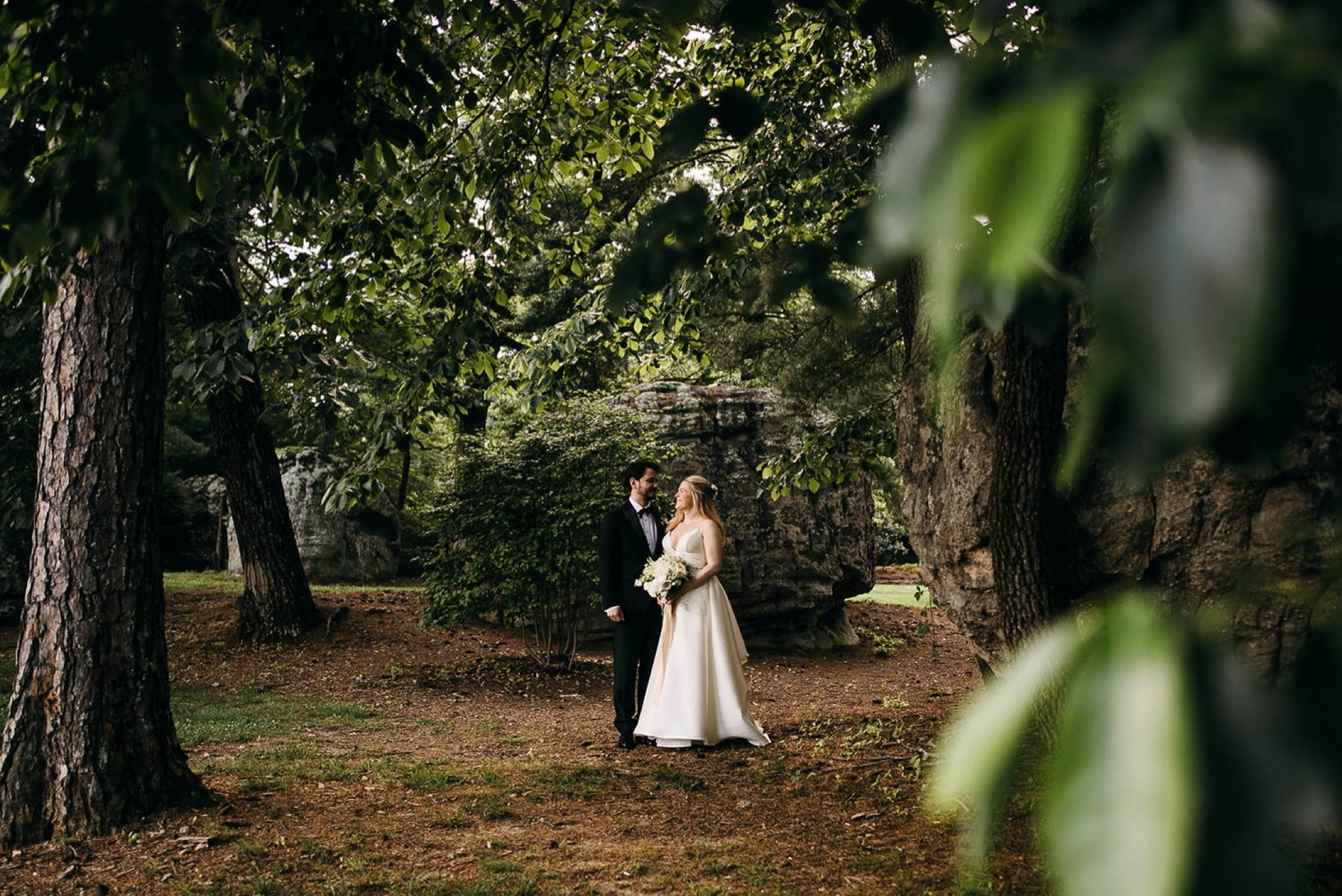 bride and groom walk beneath tall trees at their Lookout Mountain Club wedding