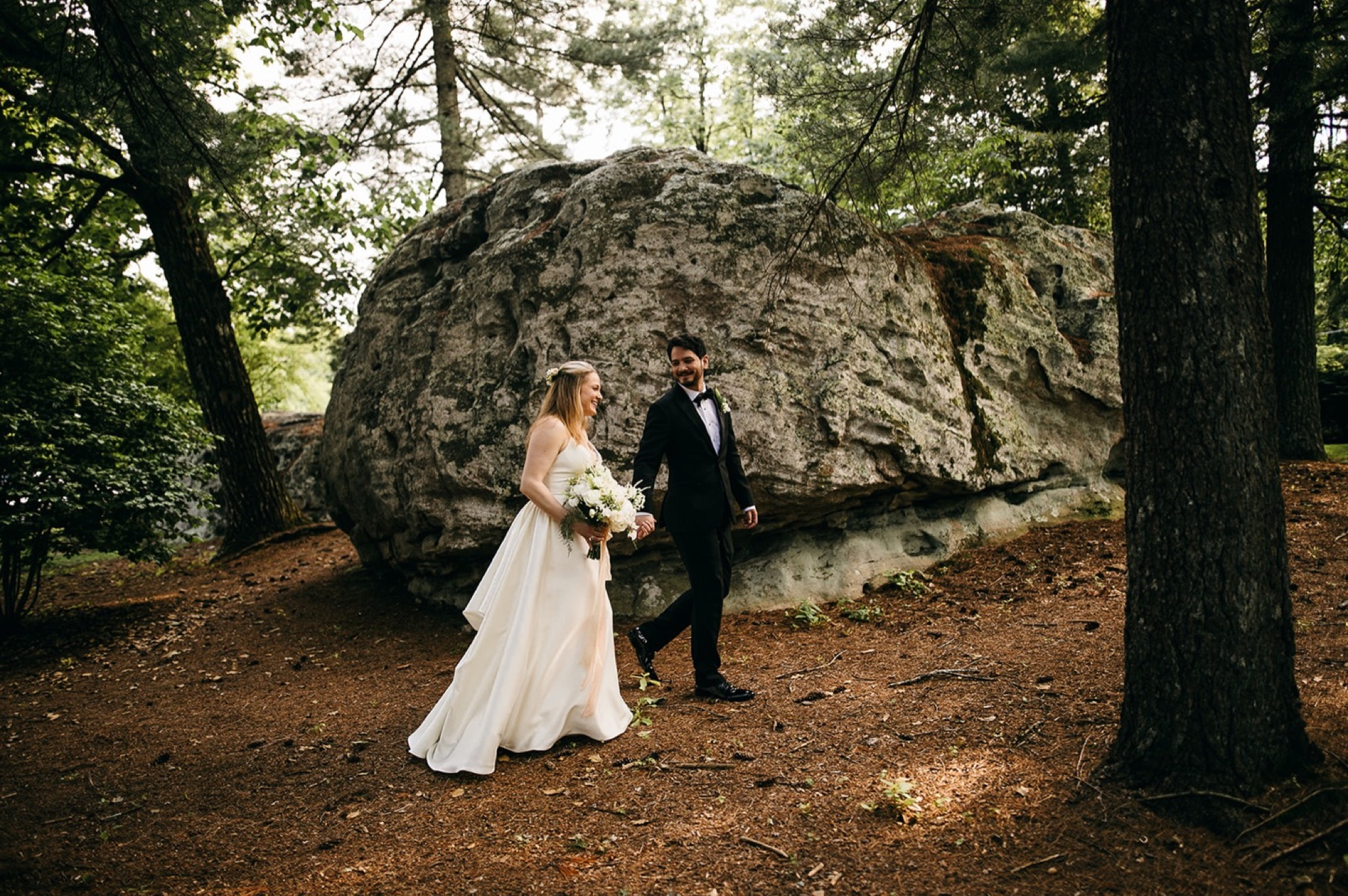 bride and groom walk beside large rocks and tall trees at Lookout Mountain Club in Chattanooga