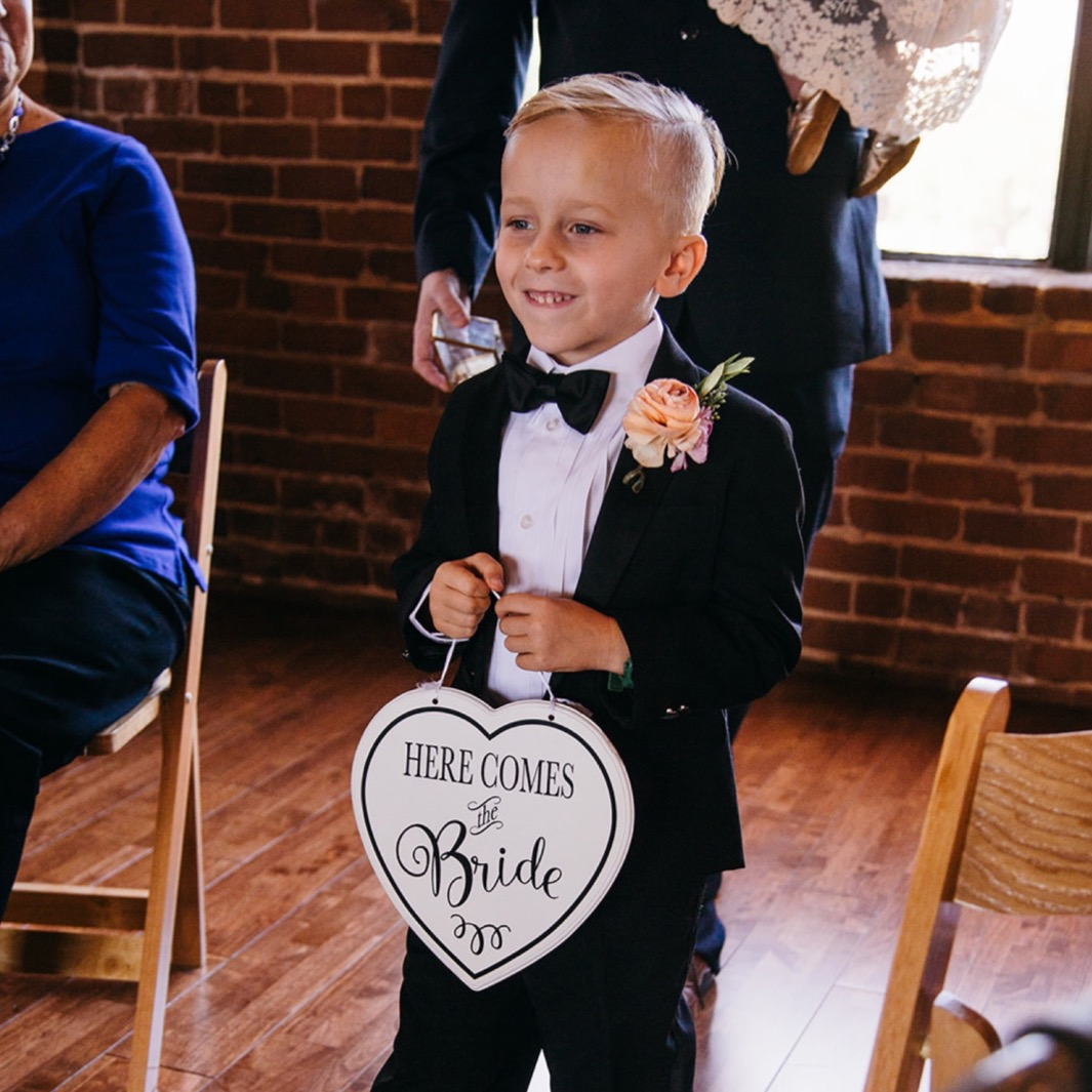 Ring bearer smiles and holds a sign as he walks down the aisle at the wedding at the Turnbull building.