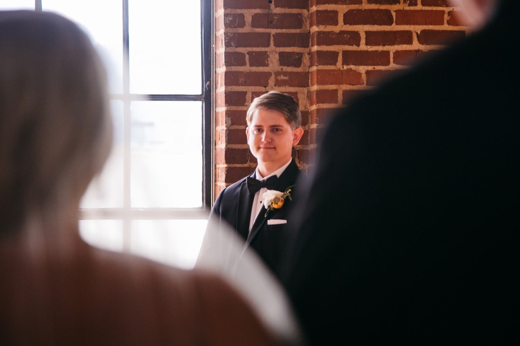 Groom smiles at his bride as she walks down the aisle during their wedding at the Turnbull building.