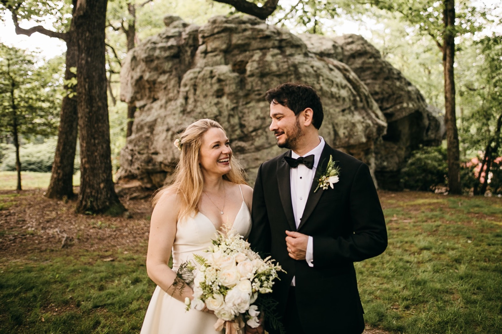 bride and groom stand in grassy field near large rocks on Lookout Mountain near Chattanooga