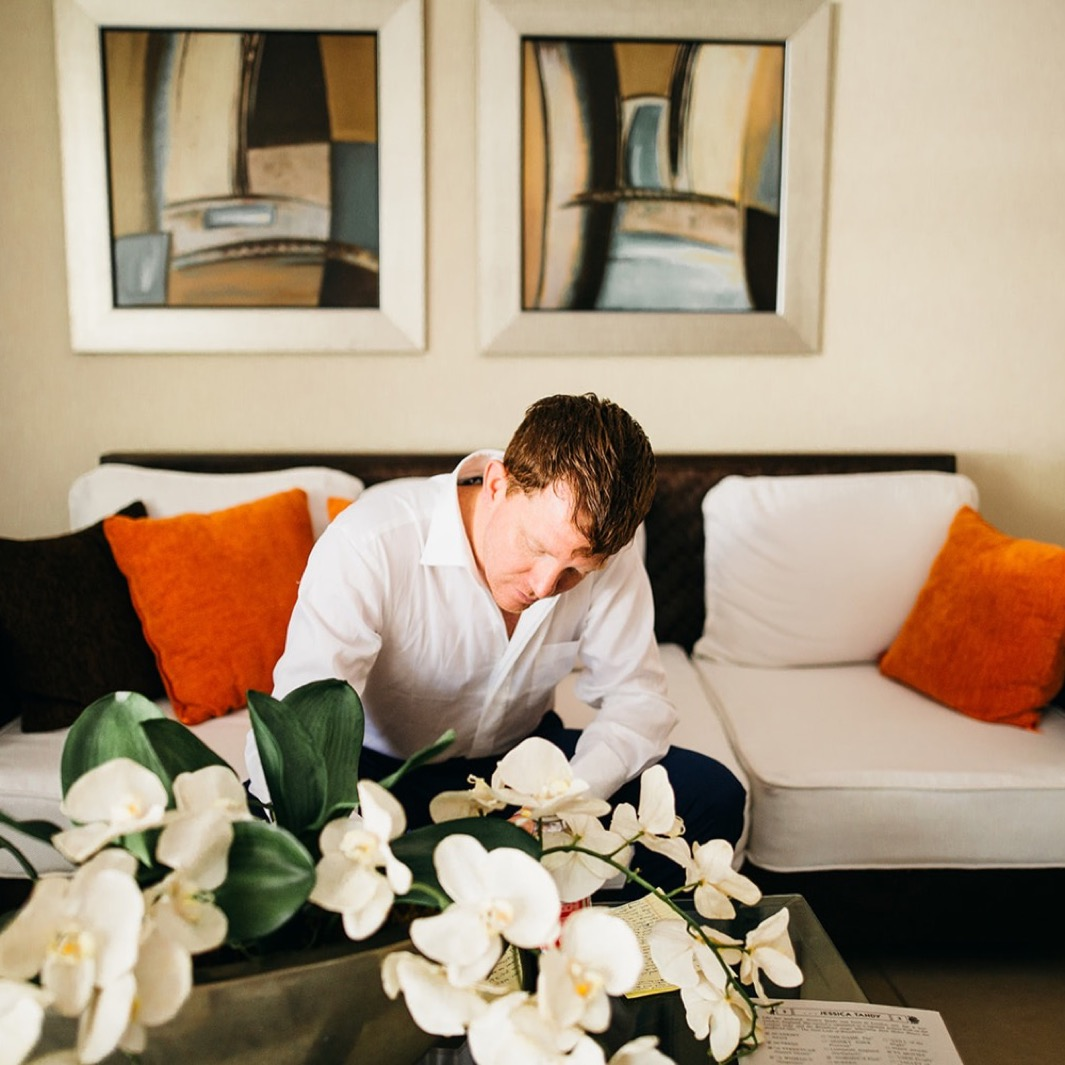 man in white button down shirt sits on a white couch behind white orchids