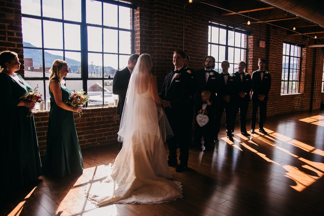The groom smiles as he holds the brides hands at the front of the alter during their wedding at the Turnbull building.