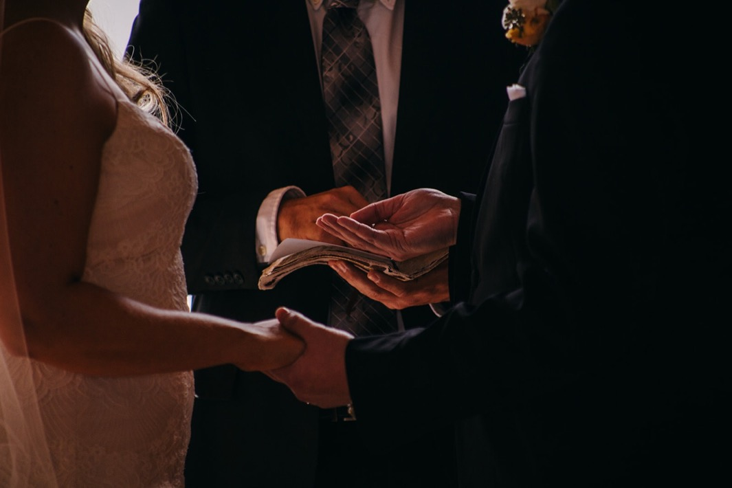 Groom holds brides ring in his hand.