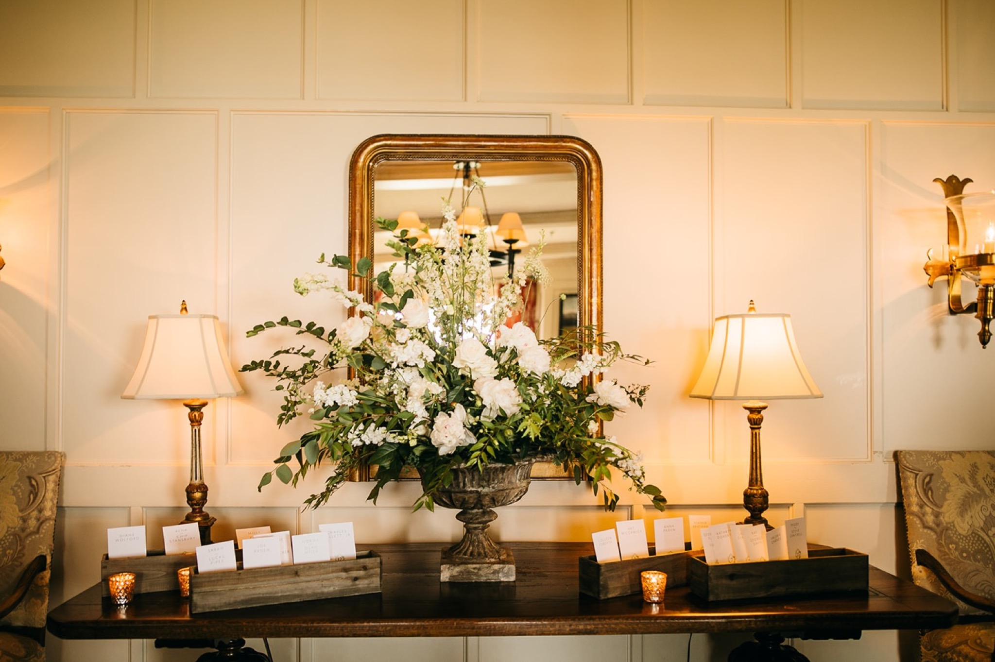 large white and green floral arrangement sits on a table in front of a mirror