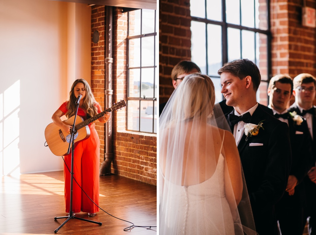 Woman is playing a guitar for the Turnbull building wedding. Groom smiles at the officiant.