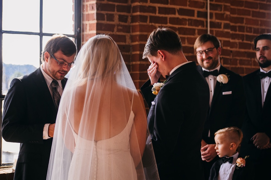 Bride and groom face the officiant as groom wipes away his tears during his wedding at the Turnbull building.