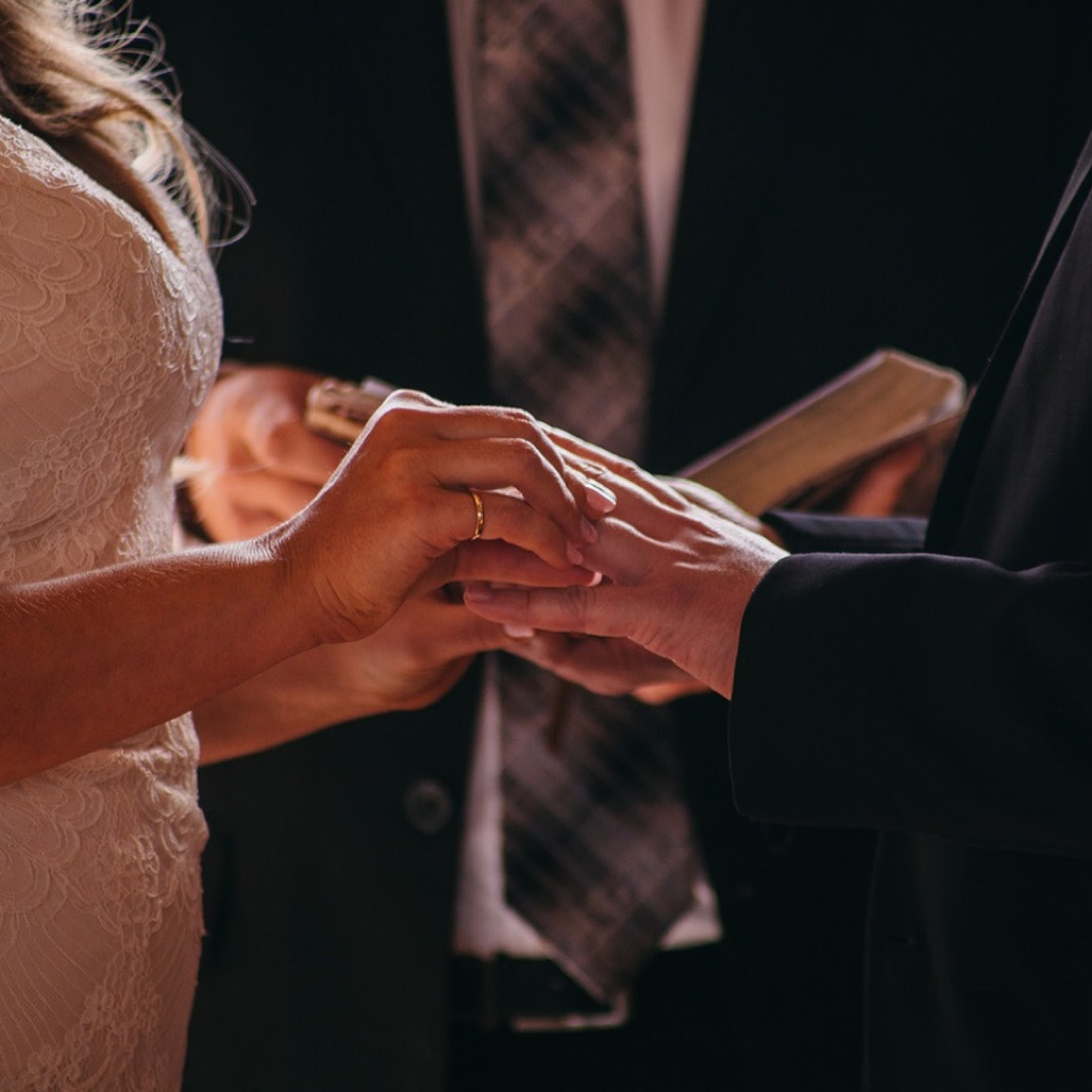 Bride puts groom's ring on his finger.