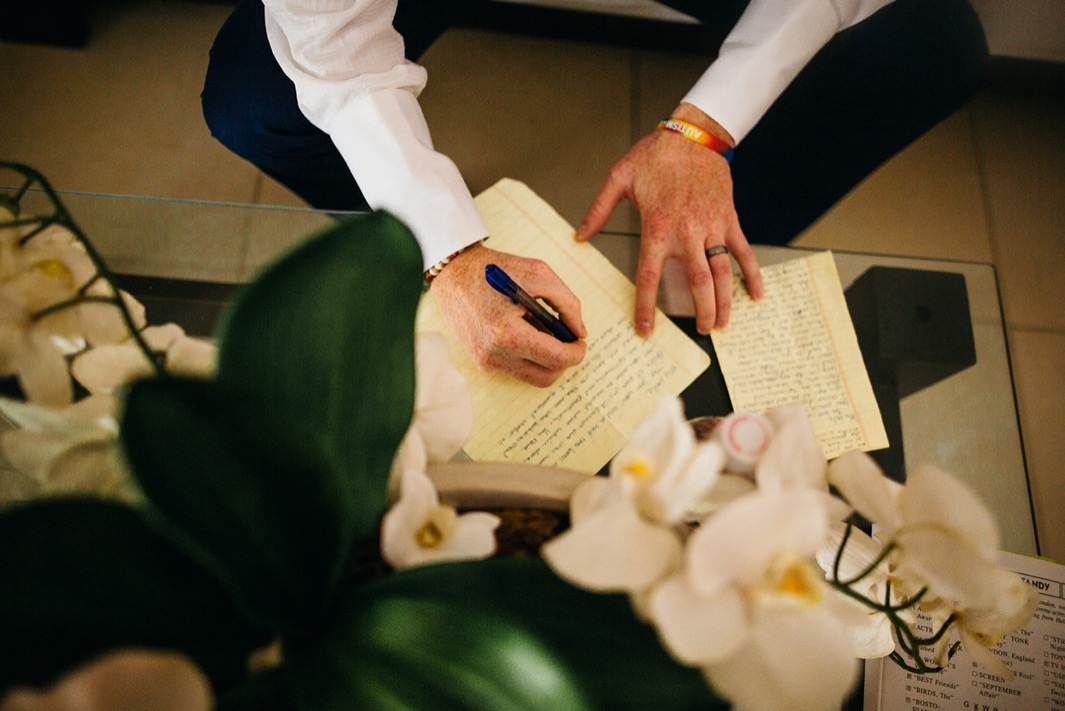 man's hands while he writes a letter on lined paper