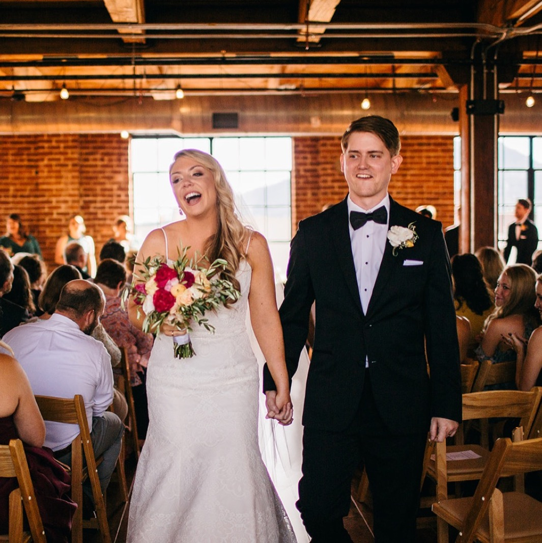 Bride and groom hold hands as they walk down the aisle of their wedding at the Turnbull building.