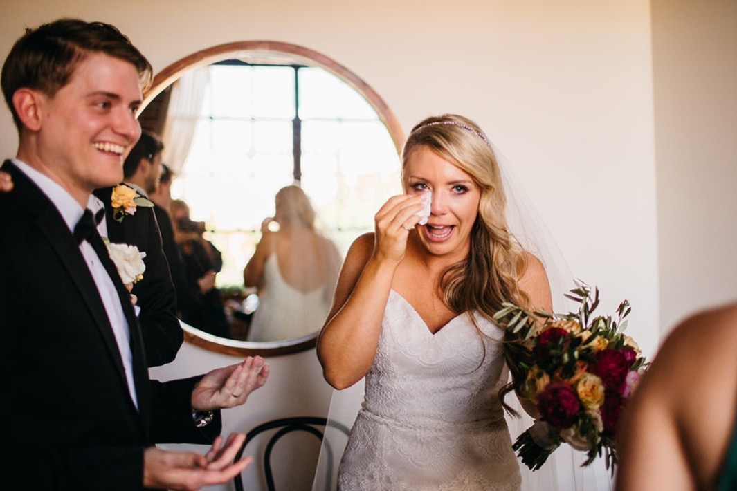 Bride wipes her tears away as groom smiles.