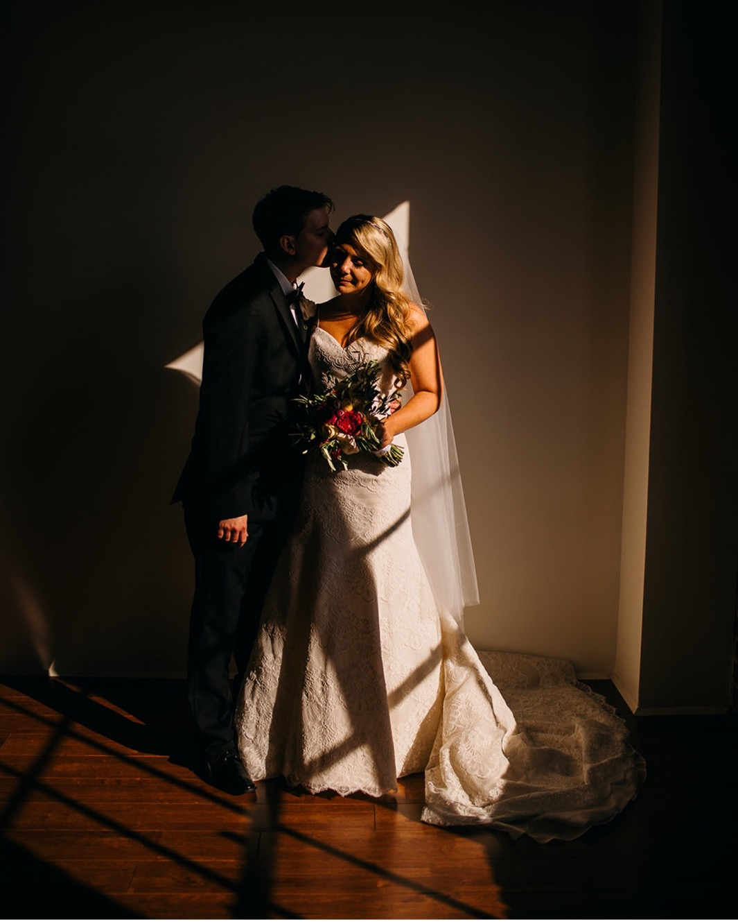 Groom kisses the brides cheek at their wedding at the Turnbull building.