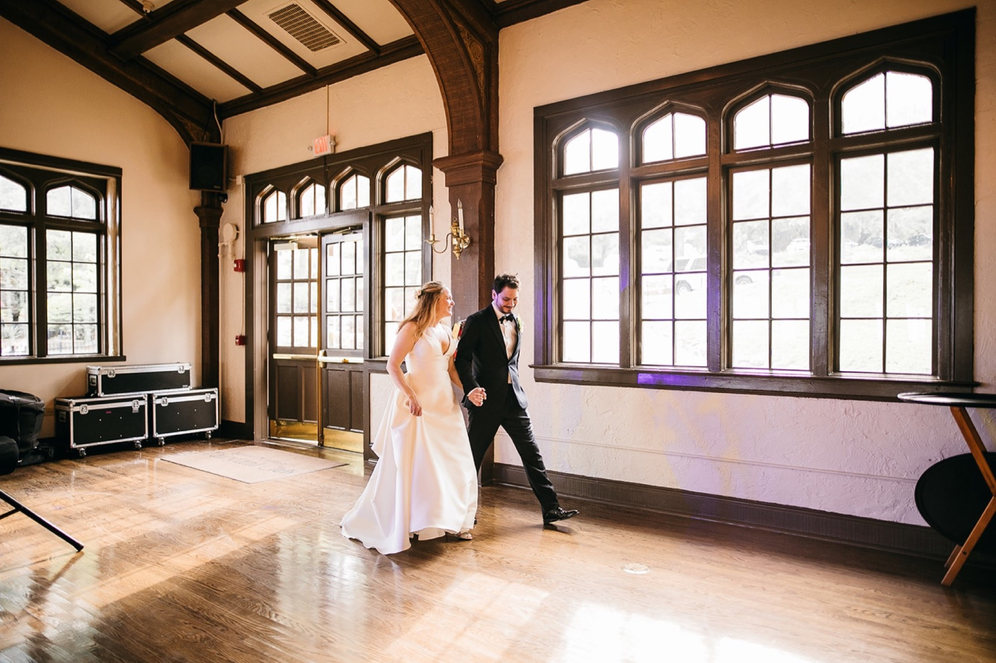 bride and groom walk along a wall of high windows at their Lookout Mountain Club wedding reception