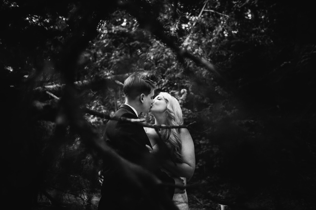 Bride and groom stand behind a tree as they share a kiss during their wedding at the Turnbull building.