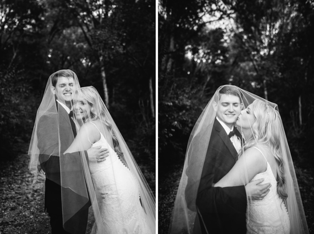 Groom holds bride as they stand under her veil and smile. Bride kisses grooms cheek.