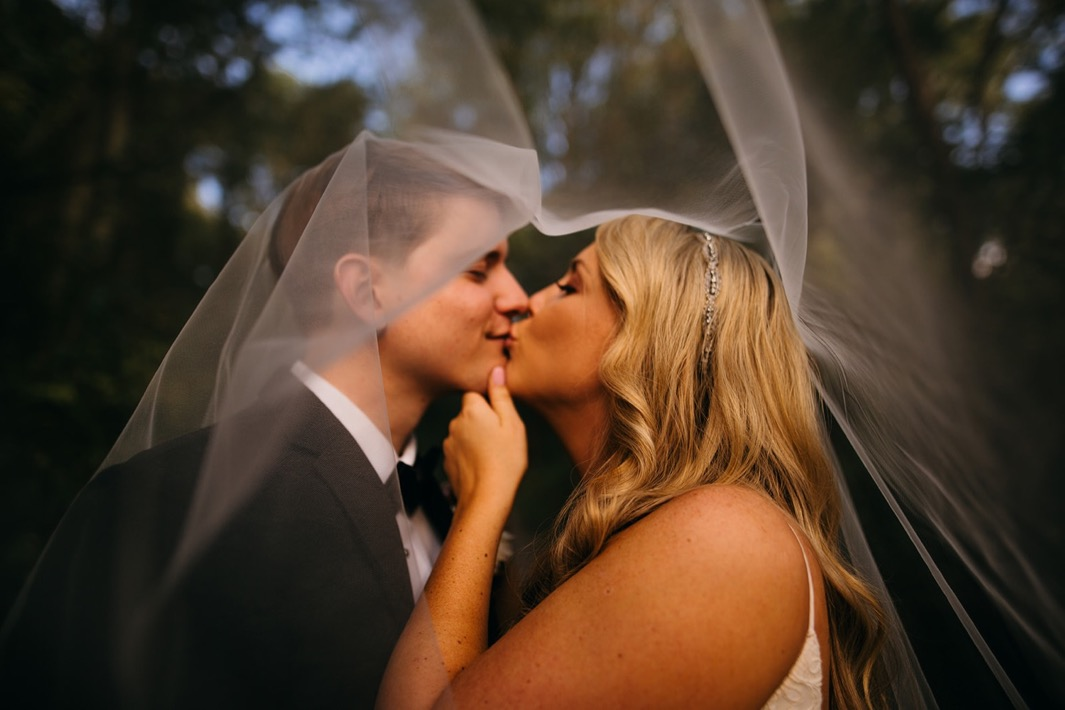 Bride holds grooms face as they share a kiss under her veil outside their Turnbull building wedding.