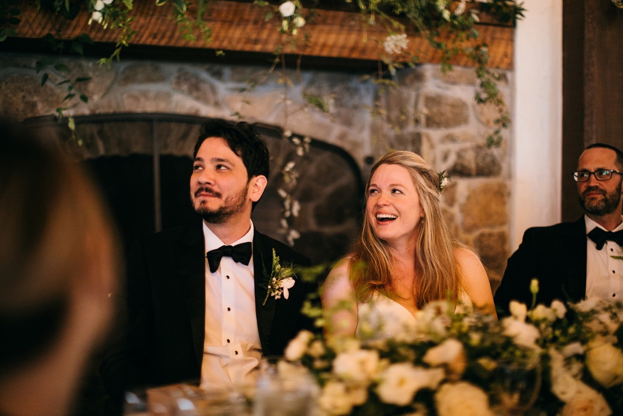 bride and groom smile while wedding guests look on