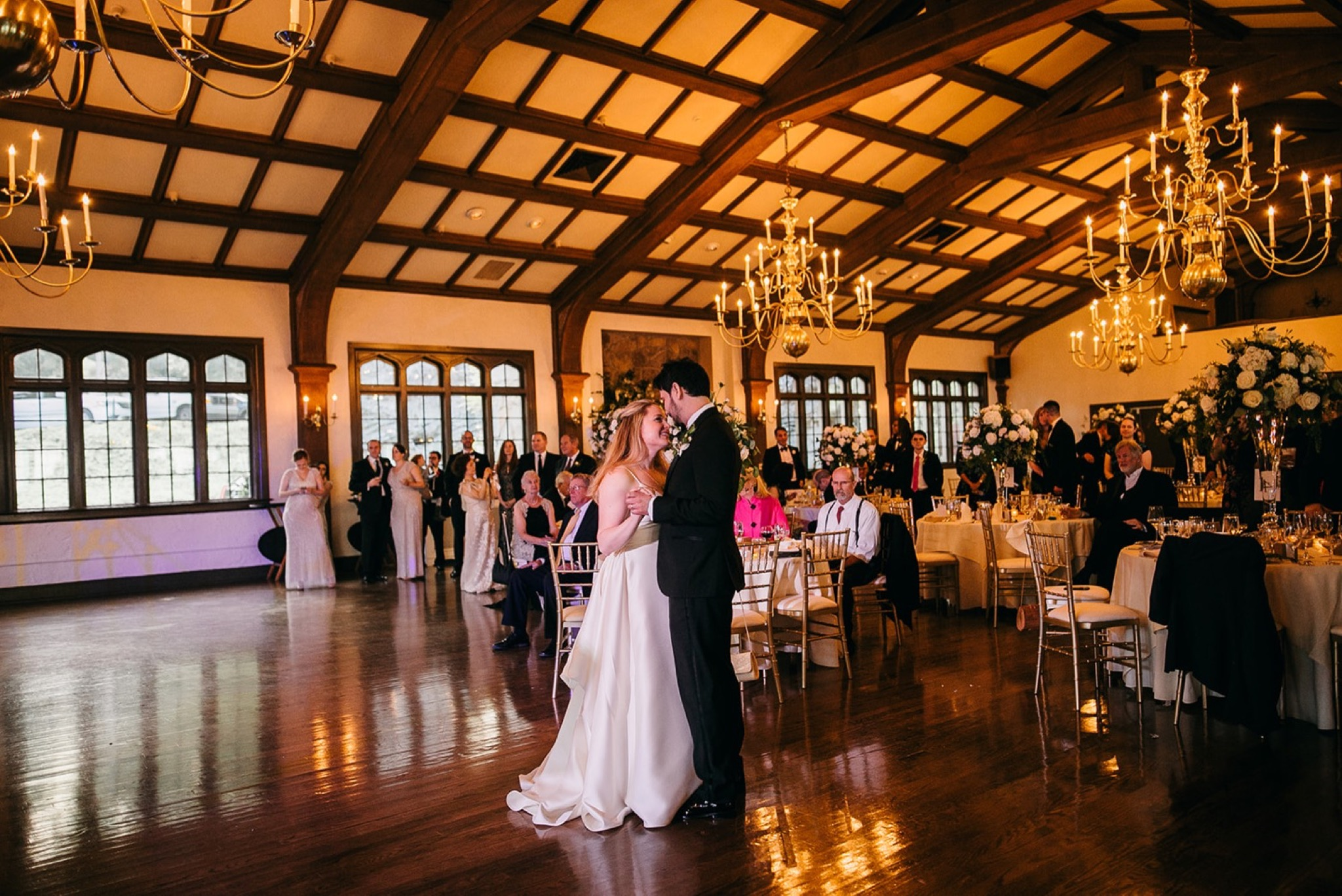 bride and groom share first dance in the ballroom at Lookout Mountain Club wedding reception while guests watch
