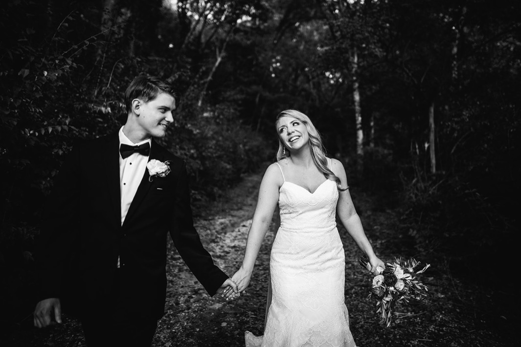 Bride and groom smile at each other as they hold hands and walk through the forest outside their wedding at the Turnbull building.